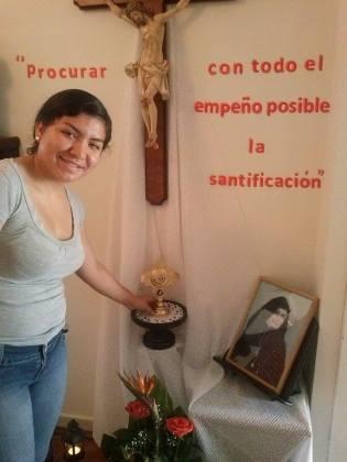 Jessifer Mendoza, , representante en este tiempo de las Jóvenes de la Residencia, coloca la Reliquia en el lugar previamente  adornado